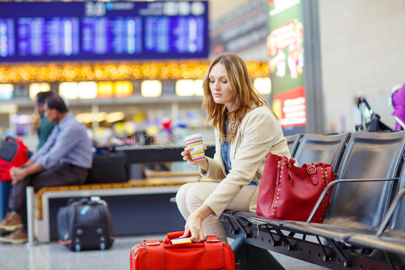 Woman at international airport waiting for flight. Tired young woman at international airport sitting and drinking coffee in terminal. Upset passenger waiting stock image