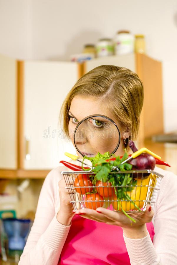 Woman investigating shopping backet with vegetables stock photo