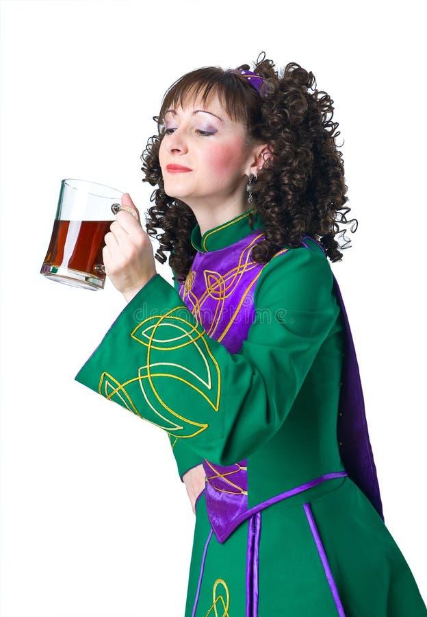 Woman irish dancer drinking beer royalty free stock images