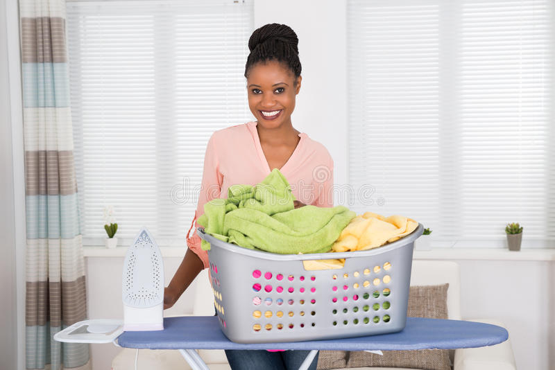 Woman With Iron And Clothes In Basket. Smiling Young African Woman With Iron And Basket Full Of Clothes stock photos