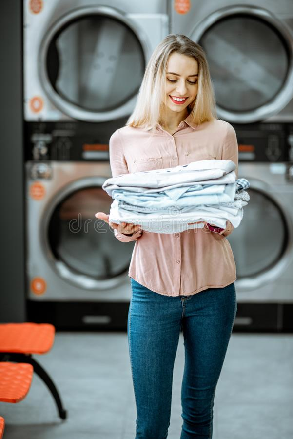 Woman with ironed clothes in the laundry. Portrait of a young woman holding ironed clothes in the professional laundry with drying machines on the background stock images