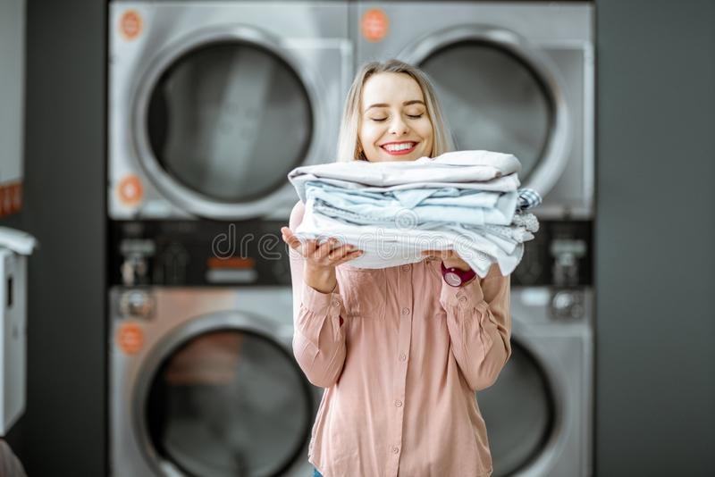 Woman with ironed clothes in the laundry. Young woman enjoying clean ironed clothes in the self serviced laundry with dryer machines on the background royalty free stock photos