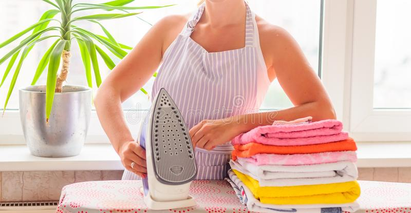 Woman ironing clothes on ironing board. Housewife woman ironing clothes on ironing board stock photo