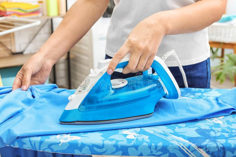 Woman ironing clothes on board indoors. Closeup stock photography