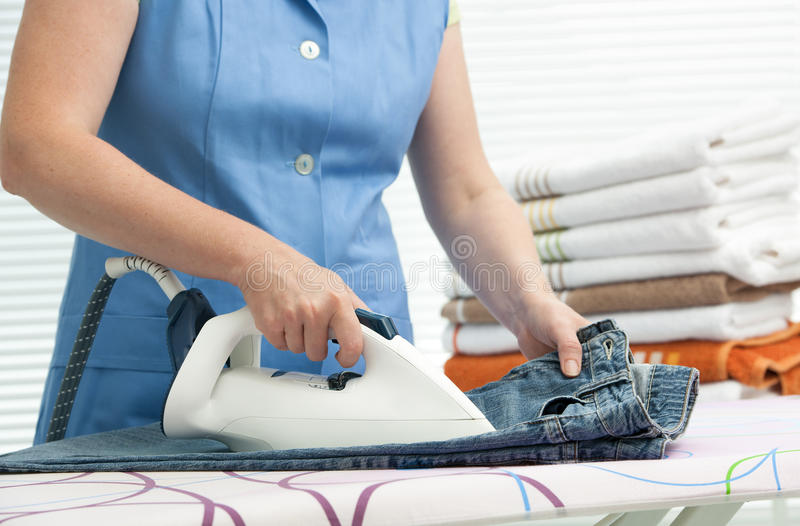 Woman ironing clothes. Close up of a woman ironing clothes with a steam iron royalty free stock photography