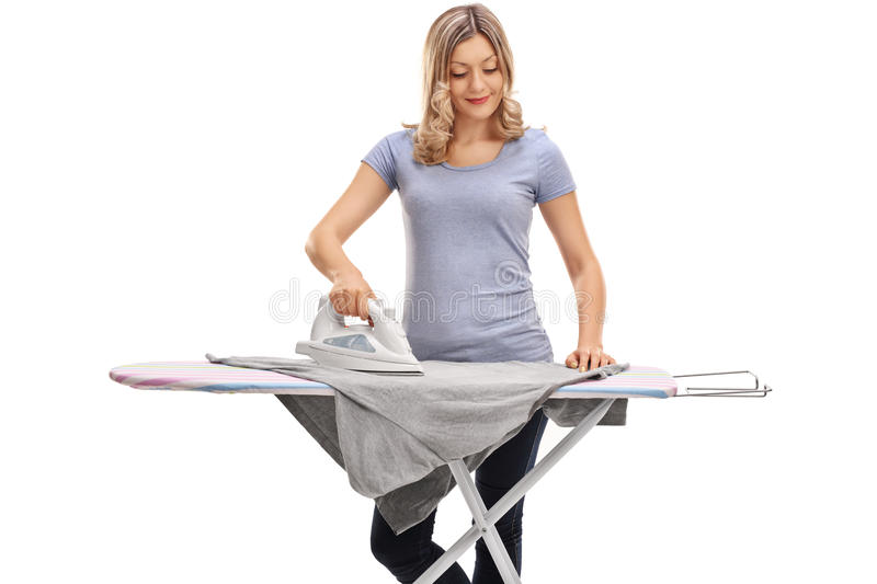 Woman ironing clothes and smiling. Cheerful woman ironing clothes and smiling isolated on white background stock image