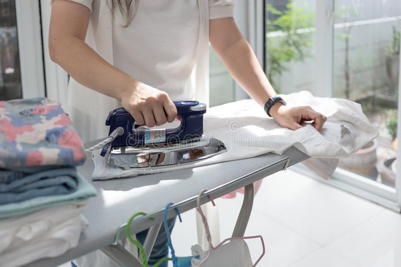 Woman ironing clothes using iron on ironing board royalty free stock photo