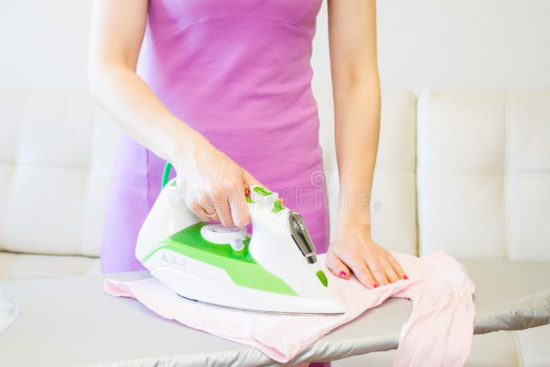 Woman Ironing Clothes Using Iron On Ironing Board. Woman Ironing kids pink Clothes Using Iron On Ironing Board After Laundry At Home stock image