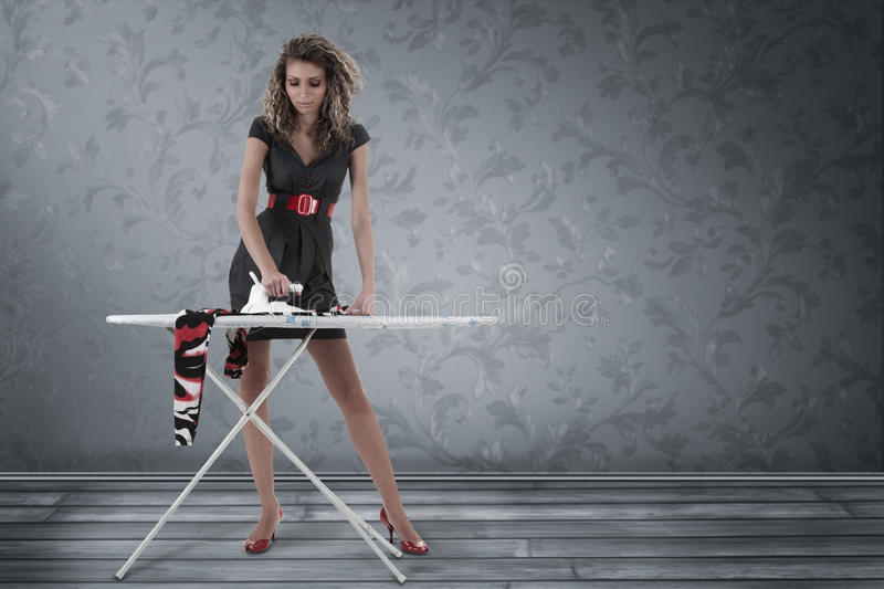 Woman ironing clothing. Beautiful woman ironing clothing in empty room stock photos