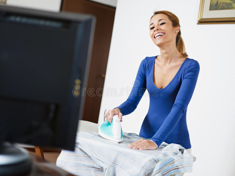 Woman ironing shirt while watching television