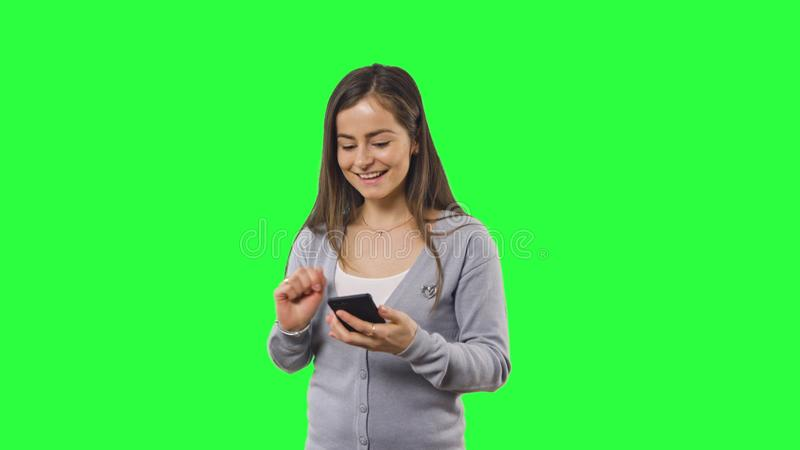 Woman isolated on green screen with phone royalty free stock image
