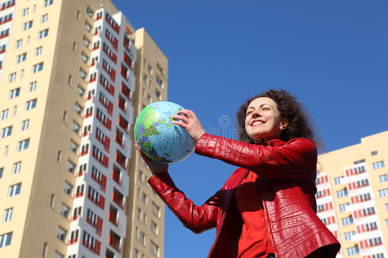 Woman in jacket holding balloon in form of globe