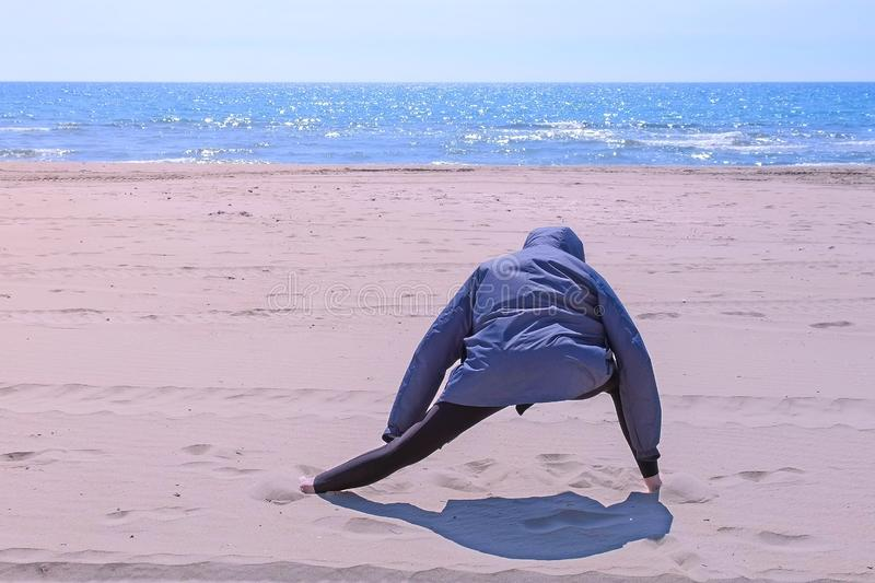 Woman in jacket is warming up on sea sand beach stretching legs, back view. Yoga exercises on the beach in windy weather. Woman in jacket is warming up on sea stock photos