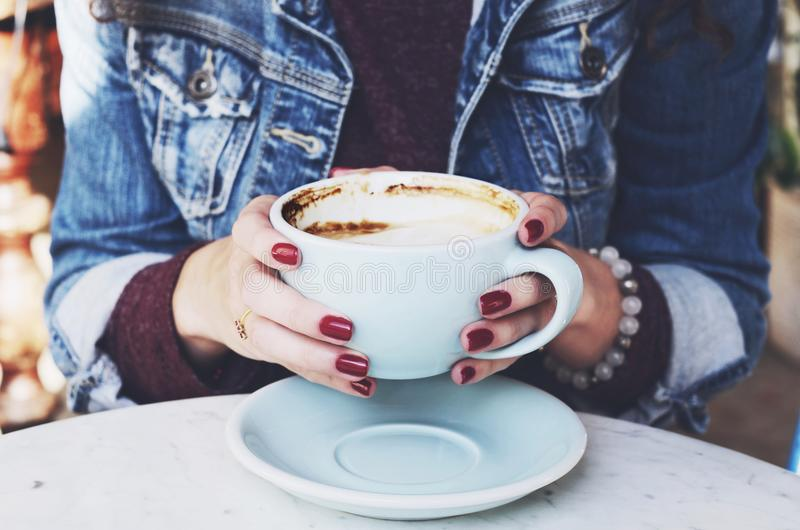 Woman in jeans jacket holding cup of cappuccino in her hands royalty free stock images