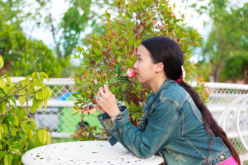 Woman in jeans shirt kissing rose stock photo