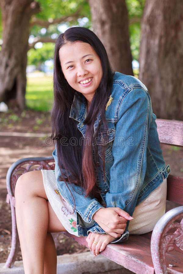Woman in jeans shirt smiling in park stock photography