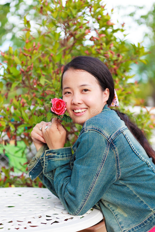 Woman in jeans shirt smiling with rose stock photo