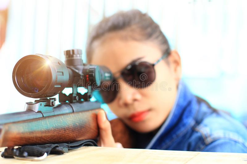 Woman in jeans suit and wearing sunglasses with the shooting range shot from a rifle gun. Girl and gun with on background,hunting sport equipment stock photo