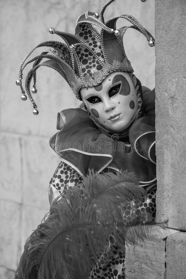 Woman in jester`s costume, mask and hat posing at the Church of San Giorgio Maggiore during Venice Carnvial stock image