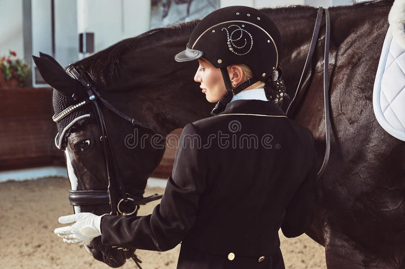 Woman jockey with his horse. In uniform for Dressage royalty free stock image