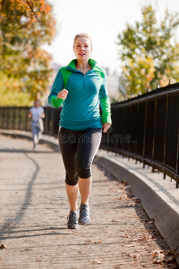Woman Jog. A woman jogging in a park royalty free stock image