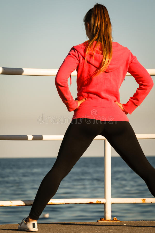 Woman jogger stretches on pier by seaside. Woman jogger athletic female taking break from running to stretch out on pier by seaside back view royalty free stock photo