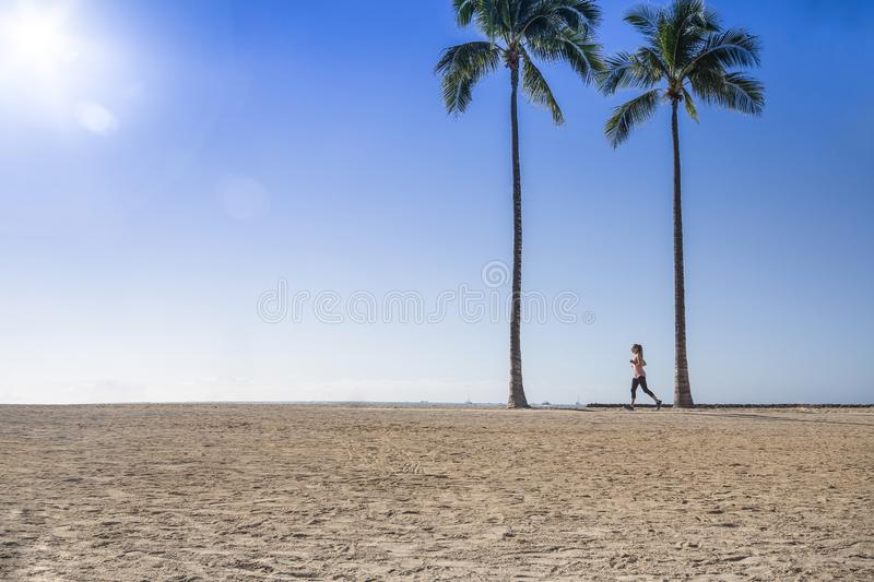 Woman jogging at the beach between two palm trees. Fitness photo Side view along the horizon. Copy space in the blue sky and sand stock photo