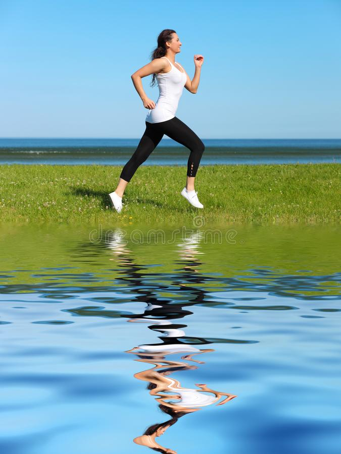 woman jogging on the beach stock images