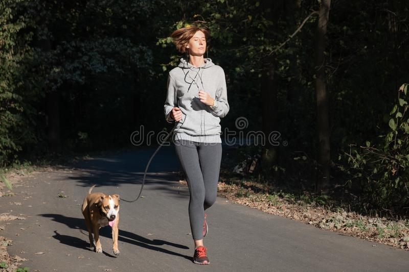 Woman jogging with dog in a park. Young female person with pet d stock photography