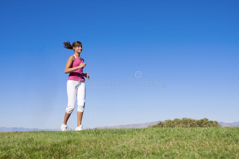 Woman Jogging Outdoors. An attractive female jogging outdoors on a calm day stock photos