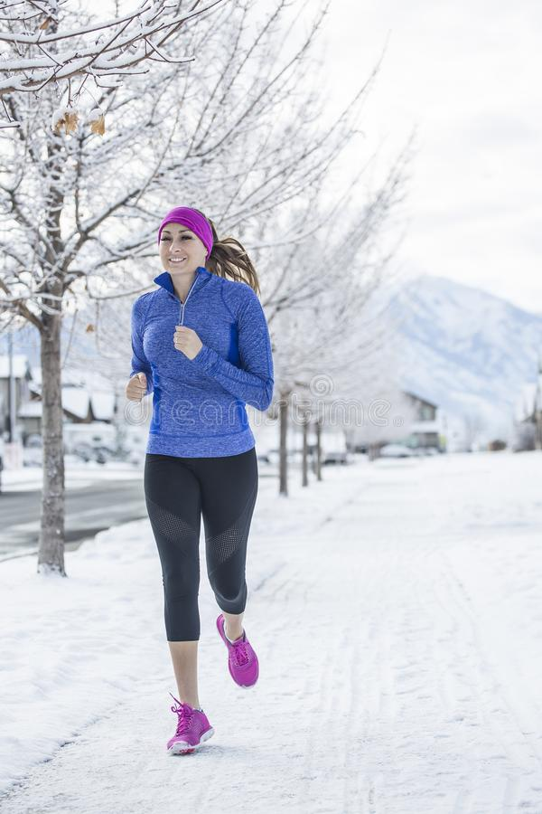 Woman jogging outdoors during winter weather and snow. Attractive Woman jogging outdoors during winter weather and snow on the ground. Vertical photo of a woman royalty free stock photography
