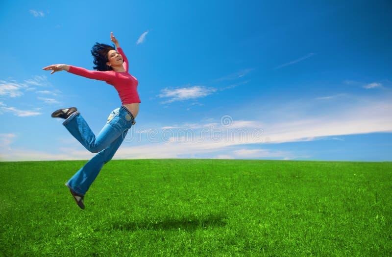Woman jump in green field stock image
