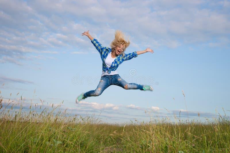 Woman jump in green grass field. Professional gymnast woman jump in green grass field stock images