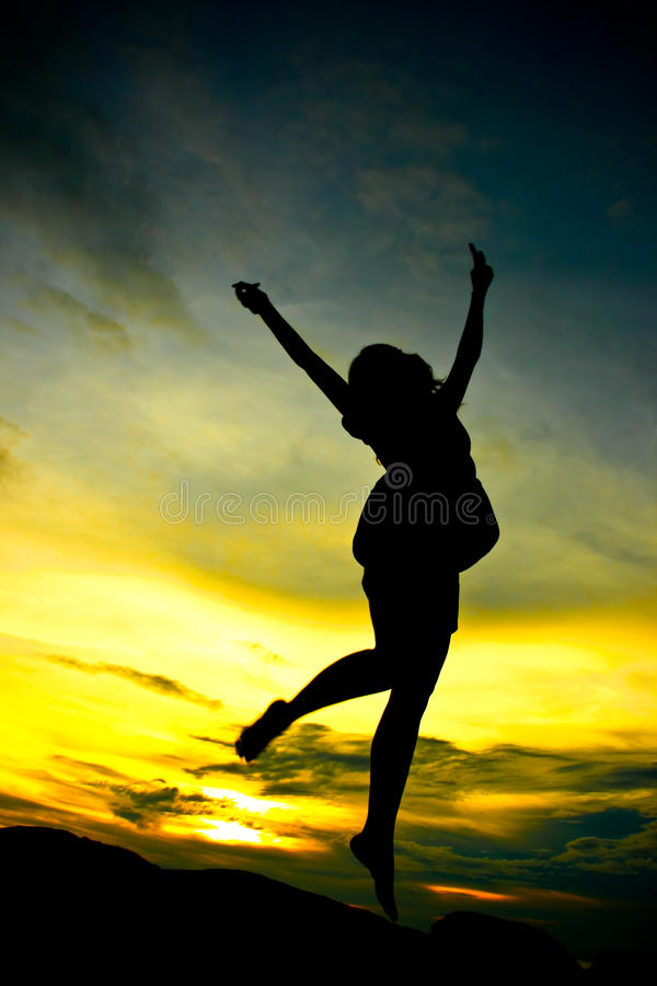 A woman jumping. A happy woman jumping at sunset silhouette royalty free stock image
