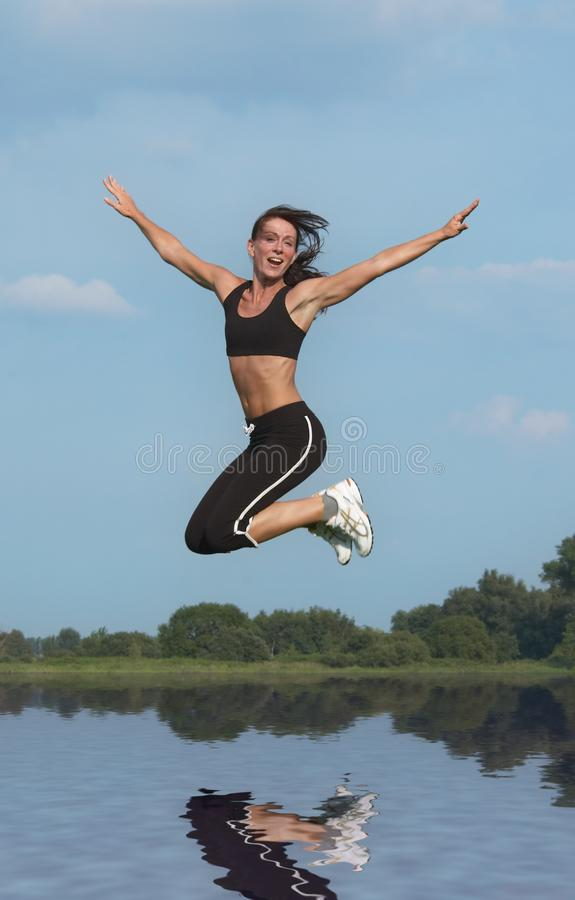 Woman jumping above water royalty free stock photos