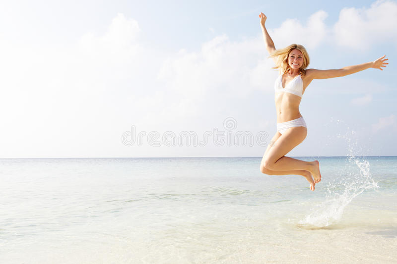 Download Woman Jumping In The Air On Tropical Beach Stock Image - Image: 32060581