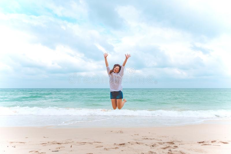 A woman jumping on the beach in front of the sea with feeling happy stock images