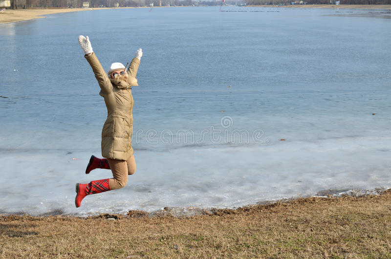 Woman Jumping on a Beach in Winter stock photography