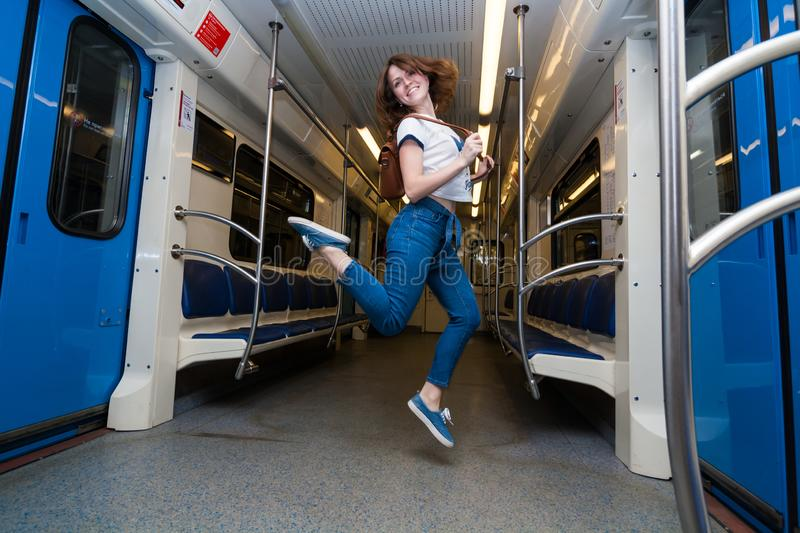 Girl jump in empty subway train. She is in blue jeans and white t-short stock image