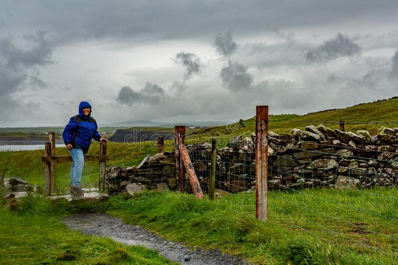 Woman jumping a fence on the coastal walk route from Doolin to the Cliffs of Moher. Geosites and geopark, Wild Atlantic Way, spring rainy day in the royalty free stock image
