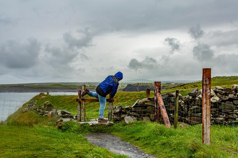 Woman jumping a fence on a rainy day on the coastal walk route from Doolin to the Cliffs of Moher. Geosites and geopark, Wild Atlantic Way, spring day in the stock photography