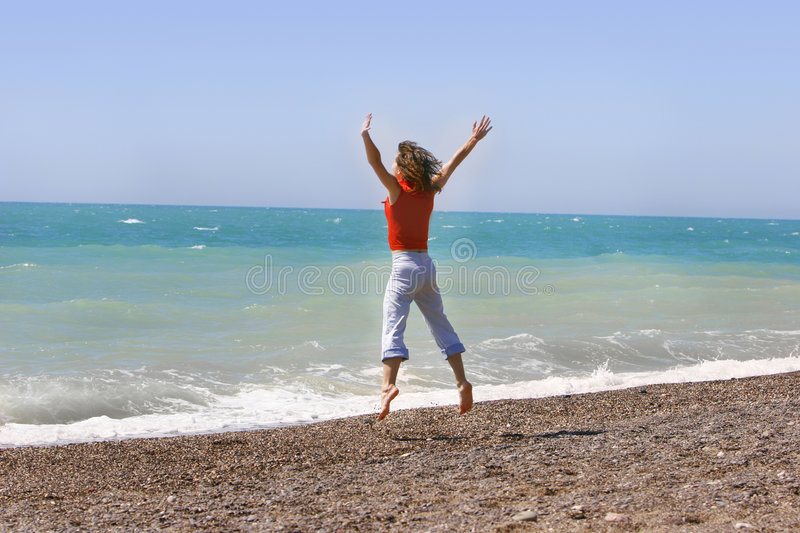 Download Woman Jumping Happily On The Beach Stock Image - Image: 5208829