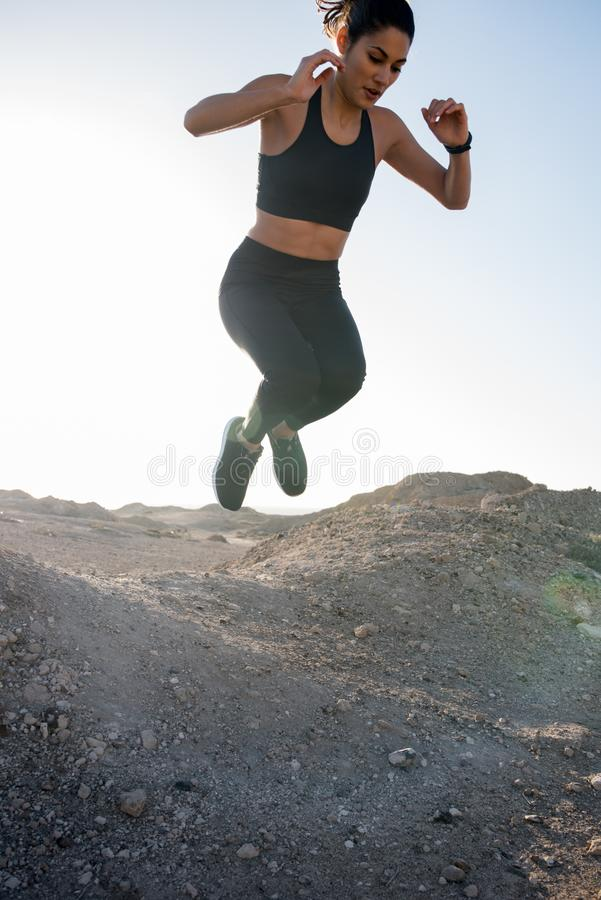 Woman jumping with her legs curled under her. Woman jumping as her legs are curled up beneath her in the desert royalty free stock photo