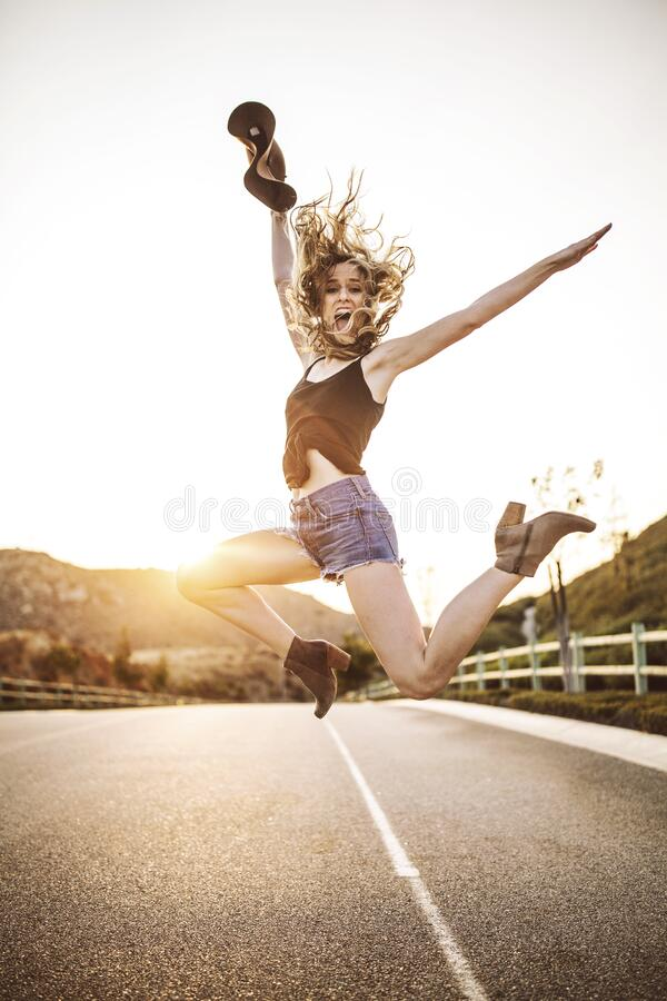 Woman jumping on highway royalty free stock images