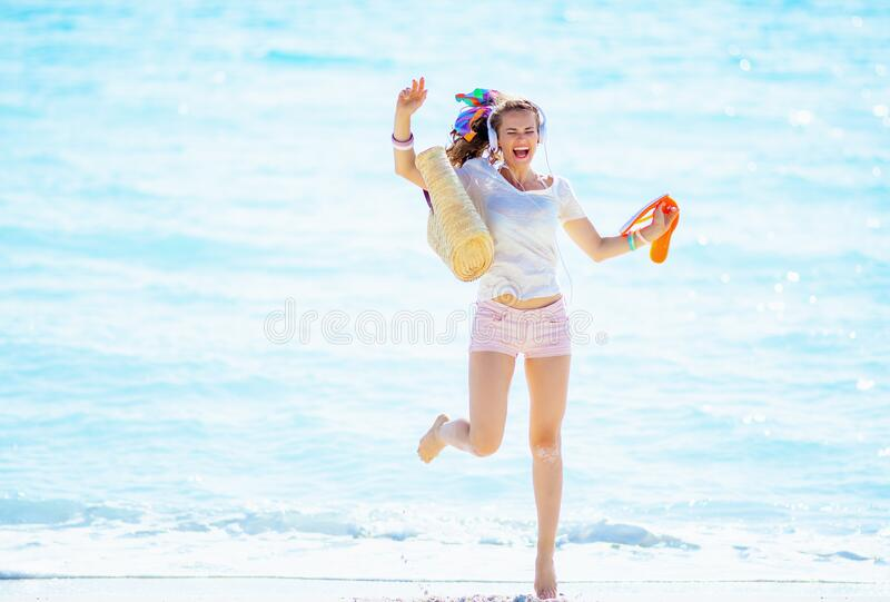 Woman jumping while listening to music with headphone royalty free stock photos