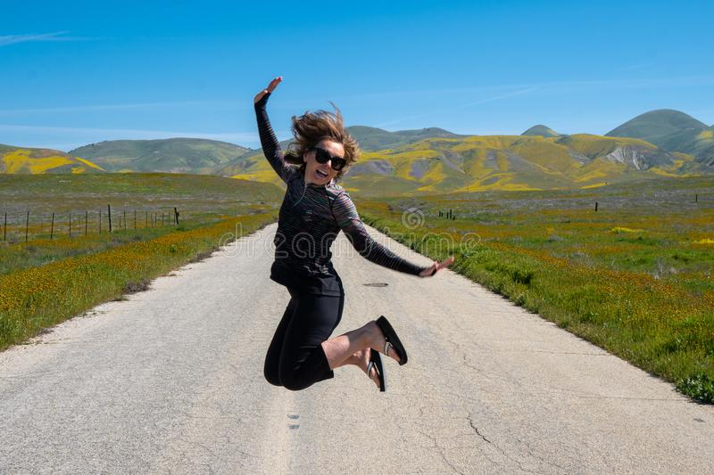 Woman jumping in the middle of the empty road in Carrizo Plain National Monument during the California superbloom.  royalty free stock photos