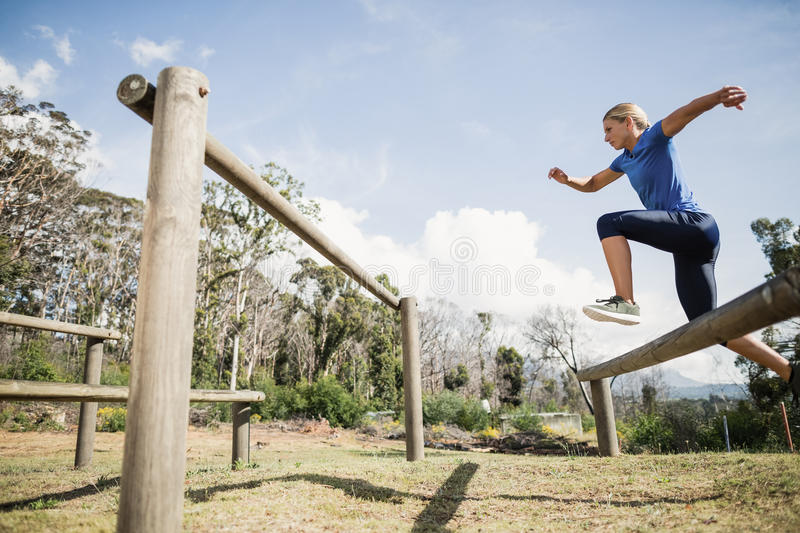 Woman jumping over the hurdles during obstacle course stock photo