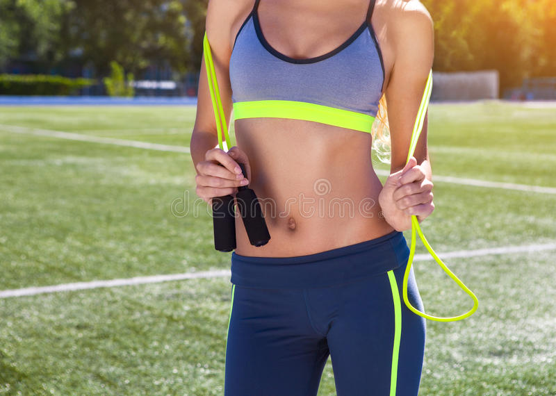 Woman with jumping rope. Beautiful young woman standing with a j royalty free stock photos