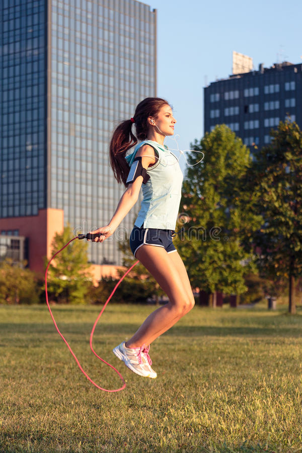 Woman with jumping rope in the city park. stock image