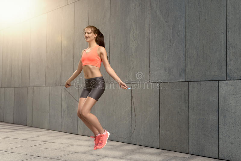 Woman jumping rope outside. Fit smiling athletic young woman in shorts and top jumping rope outside over stone block ground royalty free stock photos